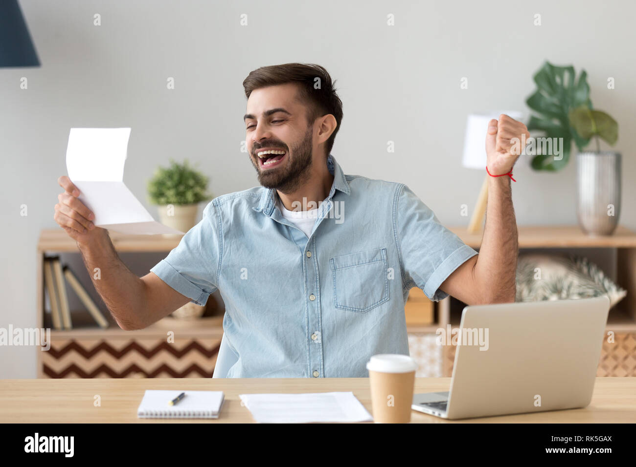 Happy young man excited reading good news holding mail letter - Stock Image