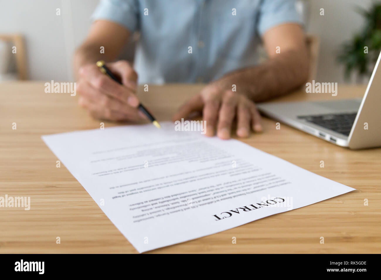Male hand signing paper contract concept, close up view - Stock Image