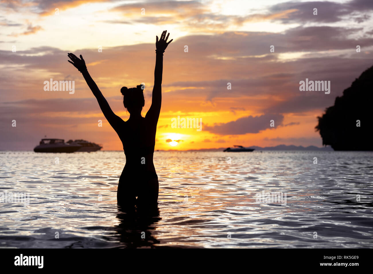 Happy slim girl stands with raised arms at sea beach and meeting sunset Stock Photo
