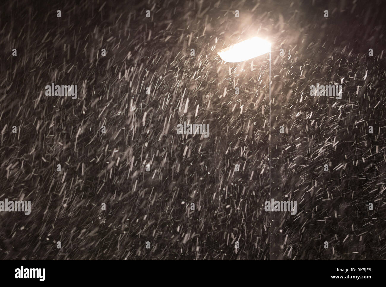 Snow falling at night by a lamppost. - Stock Image