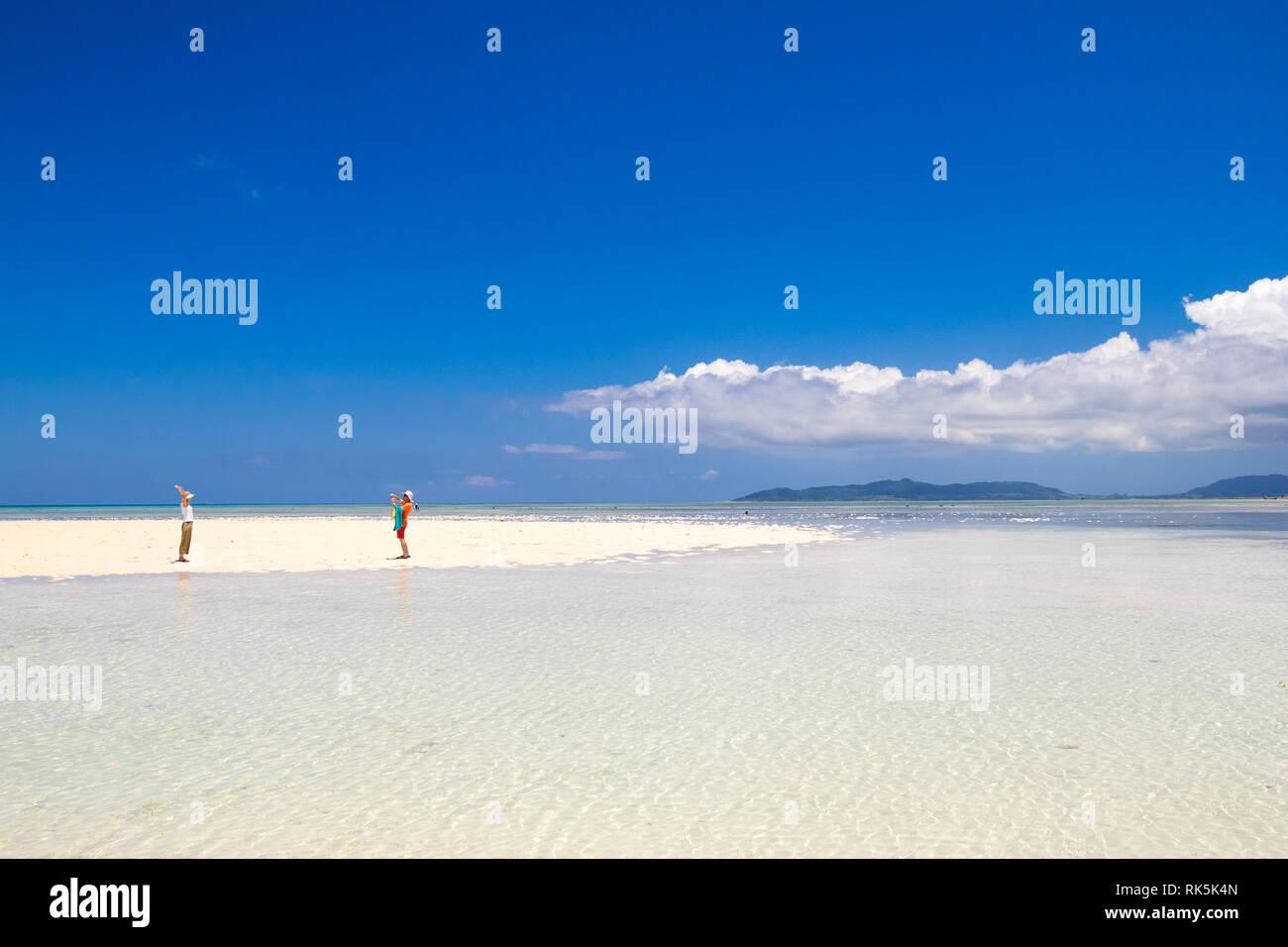 A couple on a spit of white sand by clear turquoise waters. Kondoi Beach, Taketomi Island (Taketomi-jima), Yaeyama Islands, Okinawa Prefecture, Japan. - Stock Image