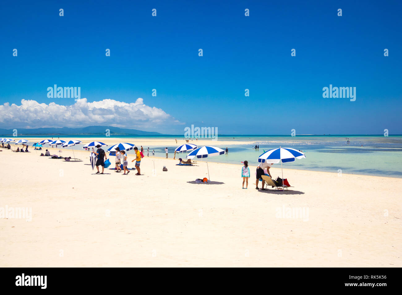 Tourists and blue and white beach umbrellas on Kondoi Beach, Taketomi Island (Taketomi-jima), Yaeyama Islands, Okinawa Prefecture, Japan. - Stock Image