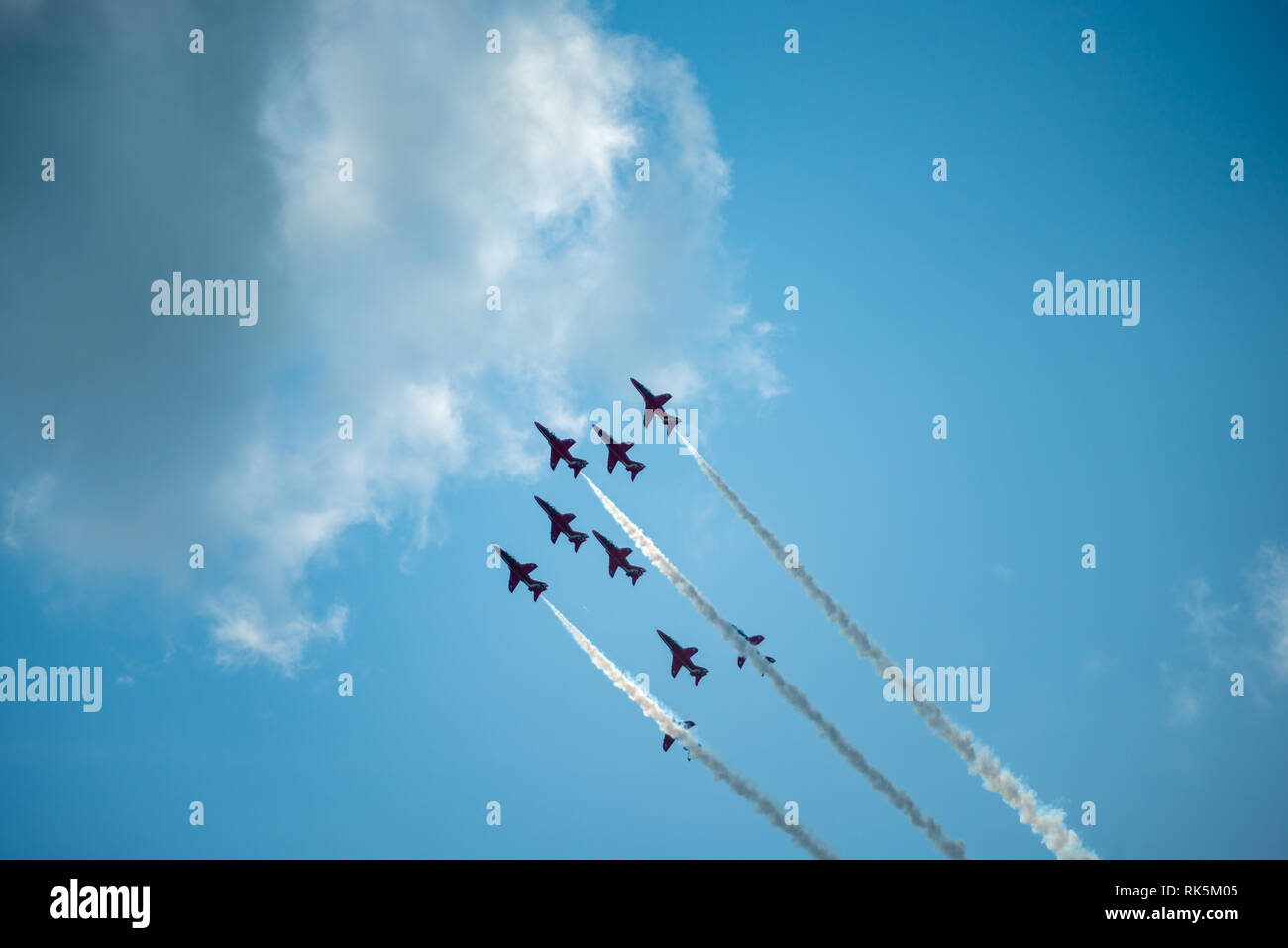 The Royal Air Force Red Arrows aeroplanes release smoke as they perform their routine at the Eastbourne Airshow in Sussex, UK. - Stock Image
