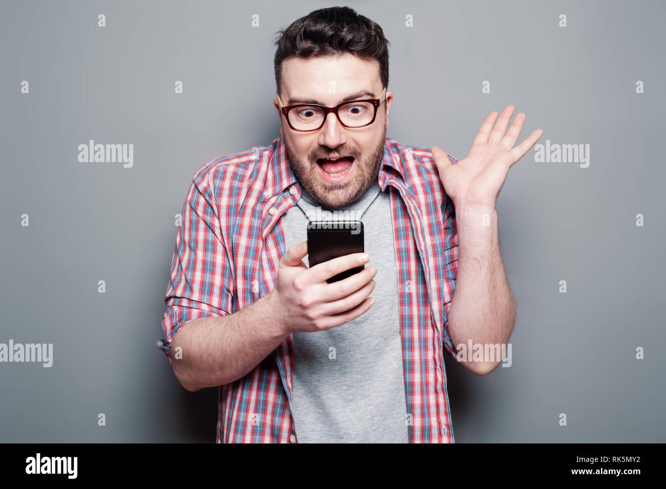 Shocked man reading message on cellphone - Stock Image
