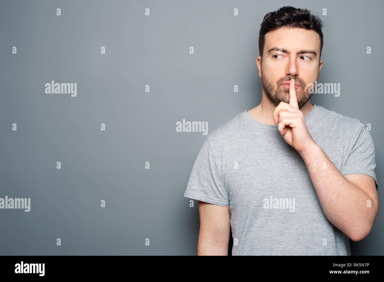 Man making silence gesture on gray background - Stock Image