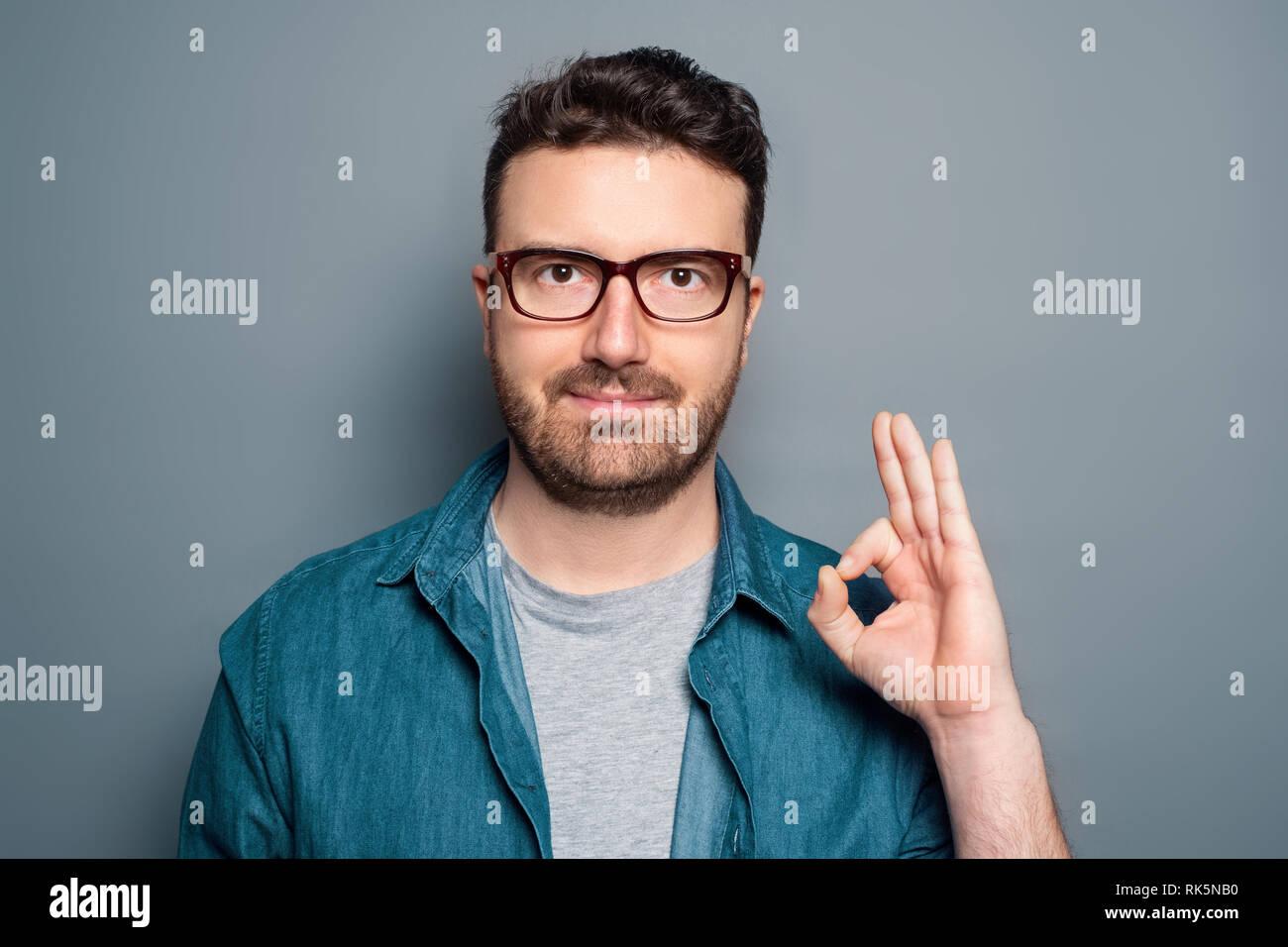 Man portrait making ok gesture isolated on background - Stock Image