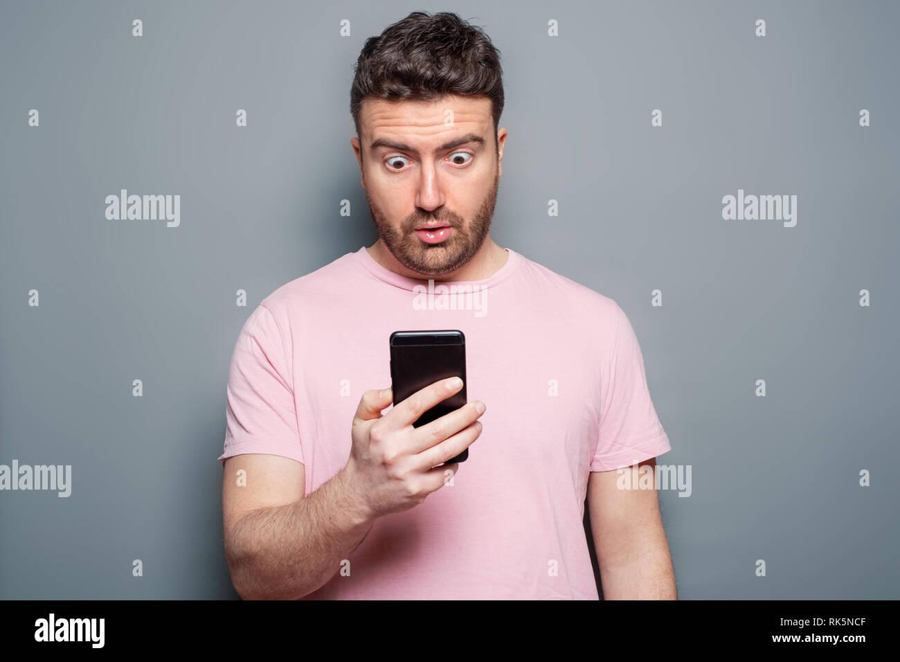 Surprised man portrait watching smartphone display - Stock Image