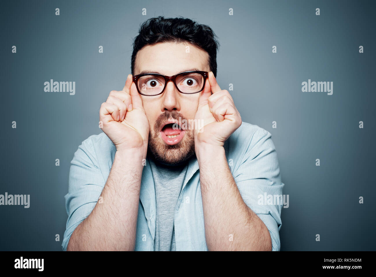 Surprised man touching glasses feeling shocked - Stock Image