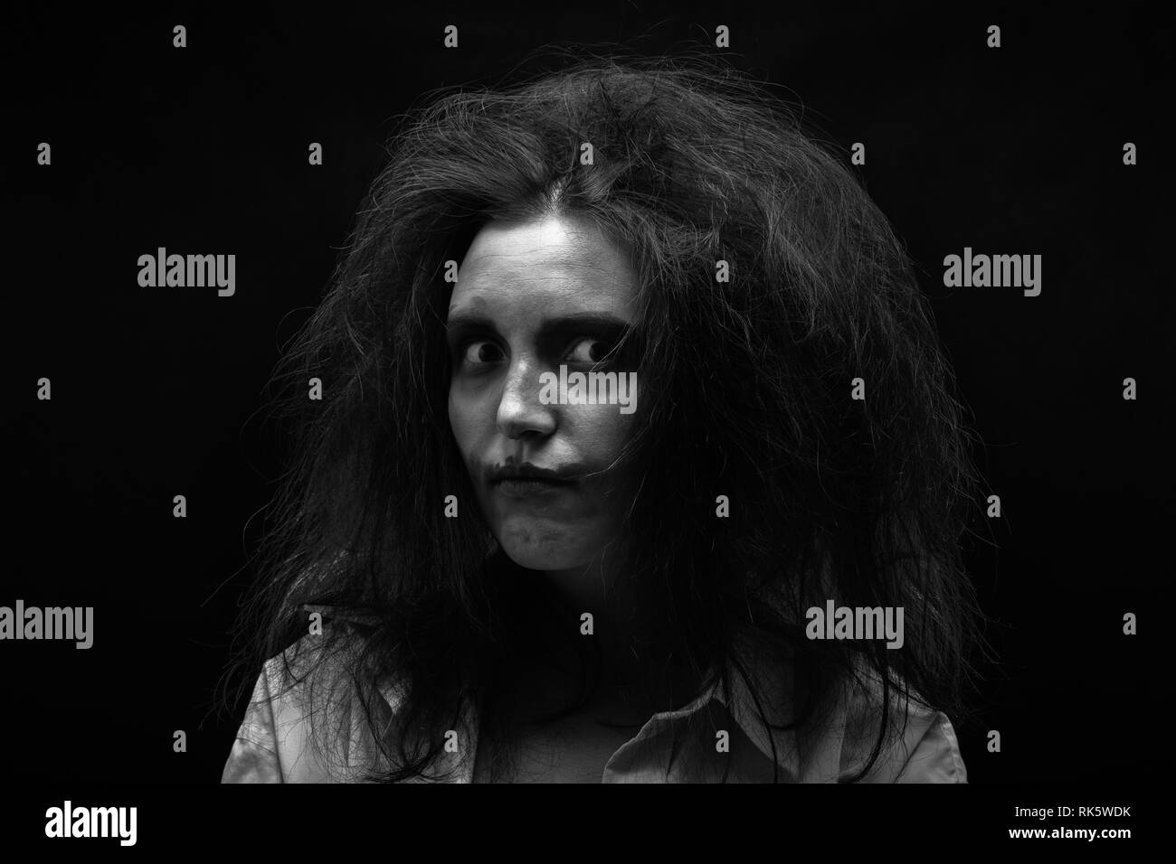 fun crazy young woman with fluffy hair on black background make shy grimace, monochrome - Stock Image