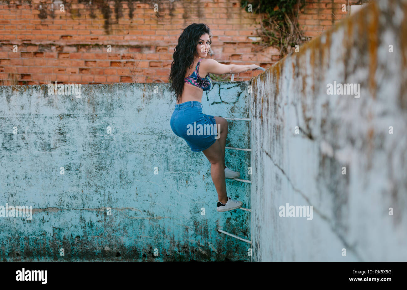 Smiling young brunette woman with bikini in an old empty pool climbing the ladder - Stock Image