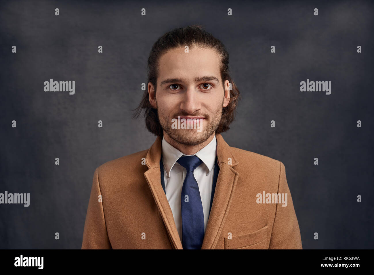 fb7b8e5b29e Portrait of a stylish young handsome long-haired unshaven man in light  brown blazer and