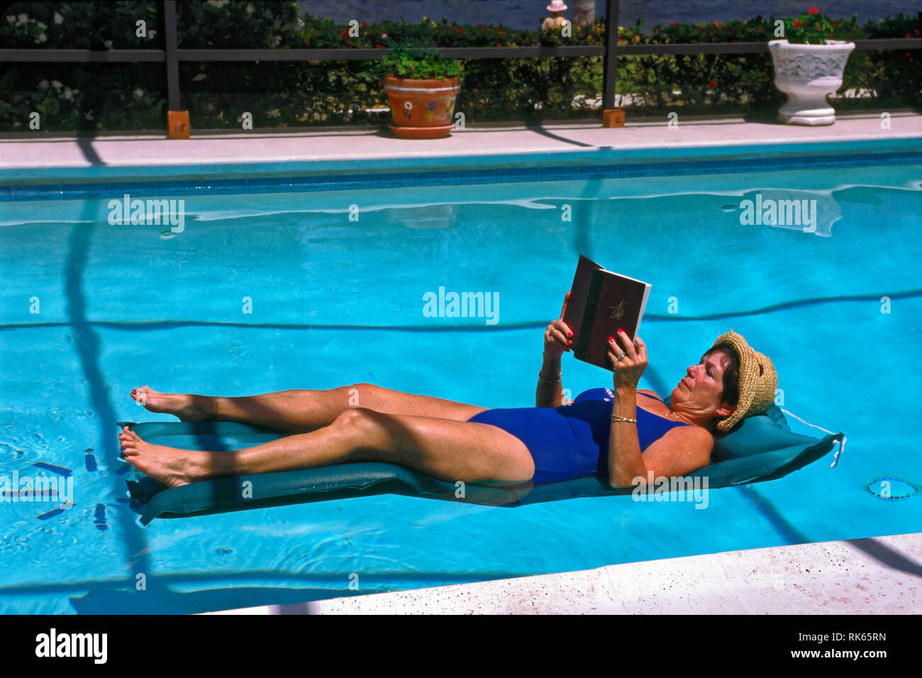 woman reading book; freckled skin, hat, pool, inflatable float; relaxing; leisure; water, restful, peaceful, horizontal; MR - Stock Image