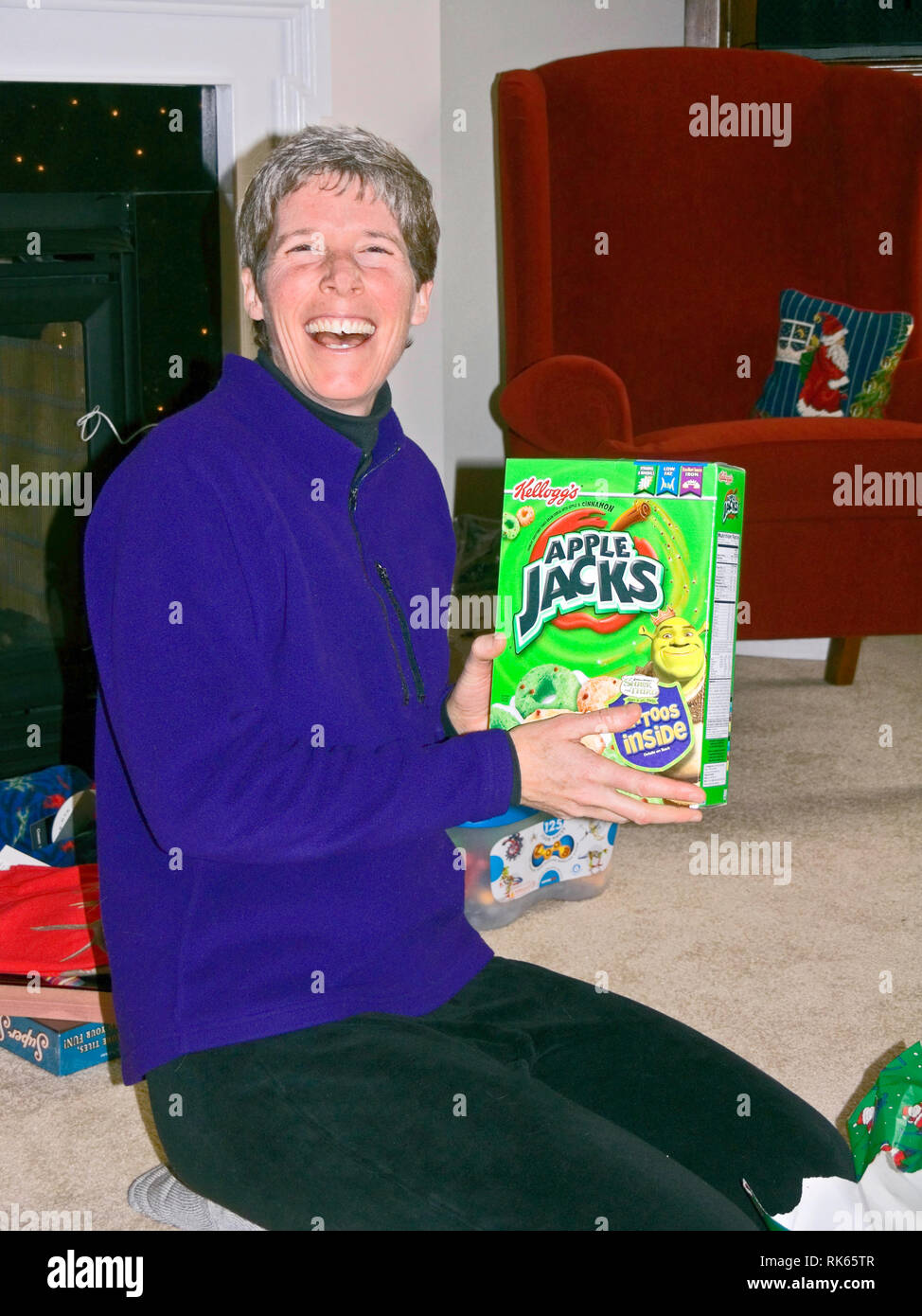 woman holding kids cereal box; laughing; gag Christmas gift; celebration, holiday, festive, fun, winter; vertical; MR - Stock Image