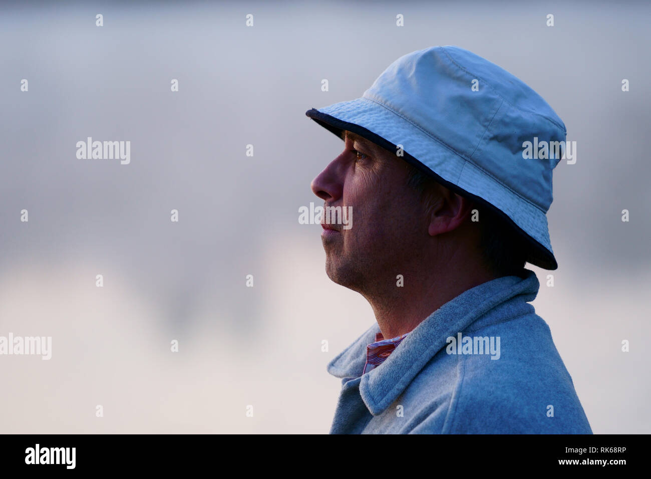 Caucasian fisherman, 50's, at the lake with fog, early morning just before sunrise. - Stock Image