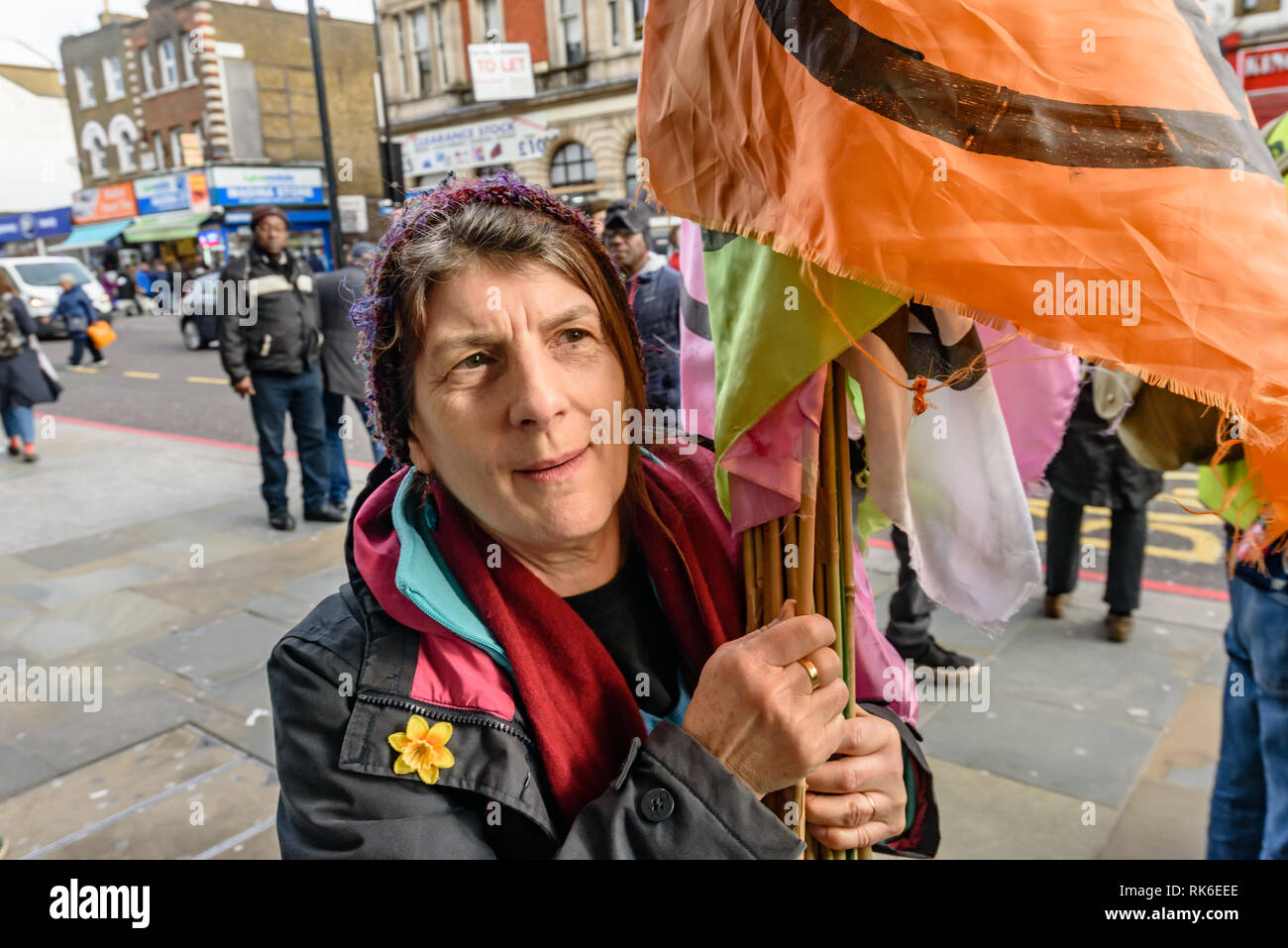 London, UK. 9th February 2019. A woman hands out Extinction Rebellion flags at the start of  a street party blocking the A10 Kingsland High St in Dalston for two hours with speeches, music and spoken word performances, t-shirt printing, face painting and free food, with dancing to a samba band which led them for a brief march up the road before returning to continue the protest in Gillett Square. XR  is in open rebellion against the UK Government for its criminal inaction in the face of impending climate and ecological collapse. Peter Marshall/Alamy Live News - Stock Image