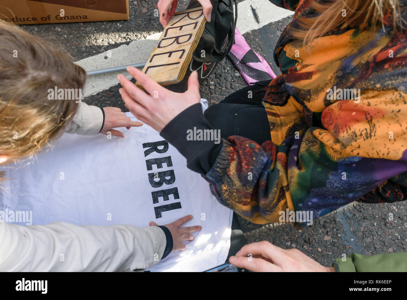 London, UK. 9th February 2019. A t-shirt is printed with the word 'REBEL' at the print workshop at the Extinction Rebellion street party blocking the A10 Kingsland High St in Dalston for two hours with speeches, music and spoken word performances, t-shirt printing, face painting and free food, with dancing to a samba band which led them for a brief march up the road before returning to continue the protest in Gillett Square.  XR is in open Rebellion against the UK Government for its criminal inaction in the face of impending climate and ecological collapse.  Peter Marshall/Alamy Live News - Stock Image