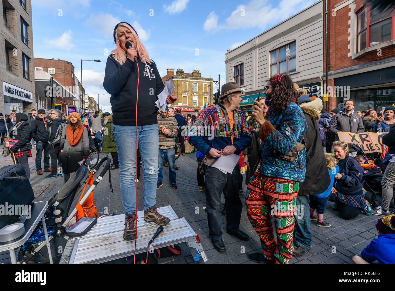 London, UK. 9th February 2019. Janie Mac speaks about refugees at the Extinction Rebellionstreet party blocking the A10 Kingsland High St in Dalston for two housrs with speeches, music and spoken word performances, t-shirt printing, face painting and free food, with dancing to a samba band which led them for a brief march up the road before returning to continue the protest in Gillett Square.  XR is in open Rebellion against the UK Government for its criminal inaction in the face of impending climate and ecological collapse.  Peter Marshall/Alamy Live News - Stock Image