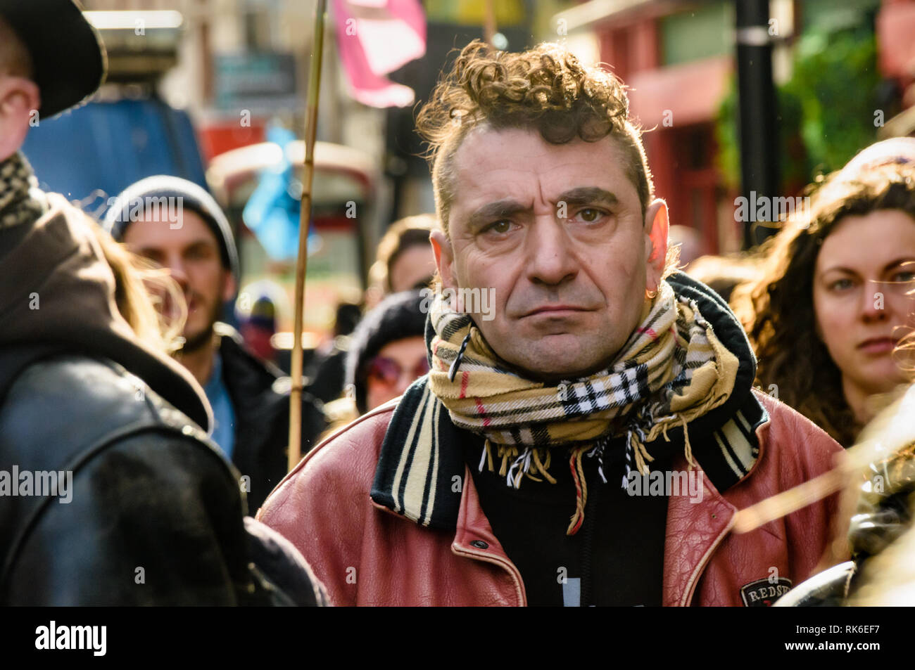 London, UK. 9th February 2019. A man listens at the Extinction Rebellionstreet party blocking the A10 Kingsland High St in Dalston for two housrs with speeches, music and spoken word performances, t-shirt printing, face painting and free food, with dancing to a samba band which led them for a brief march up the road before returning to continue the protest in Gillett Square.  XR is in open Rebellion against the UK Government for its criminal inaction in the face of impending climate and ecological collapse.  Peter Marshall/Alamy Live News - Stock Image