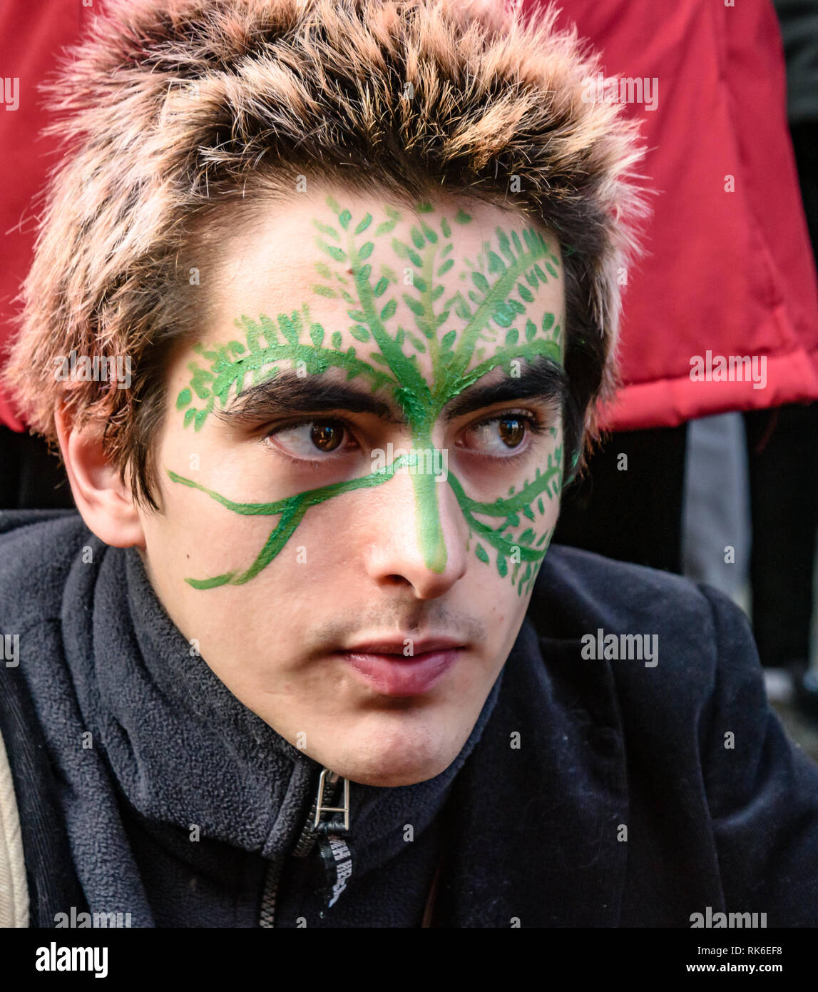 London, UK. 9th February 2019. A man having his face painted at the Extinction Rebellionstreet party blocking the A10 Kingsland High St in Dalston for two housrs with speeches, music and spoken word performances, t-shirt printing, face painting and free food, with dancing to a samba band which led them for a brief march up the road before returning to continue the protest in Gillett Square.  XR is in open Rebellion against the UK Government for its criminal inaction in the face of impending climate and ecological collapse.  Peter Marshall/Alamy Live News - Stock Image