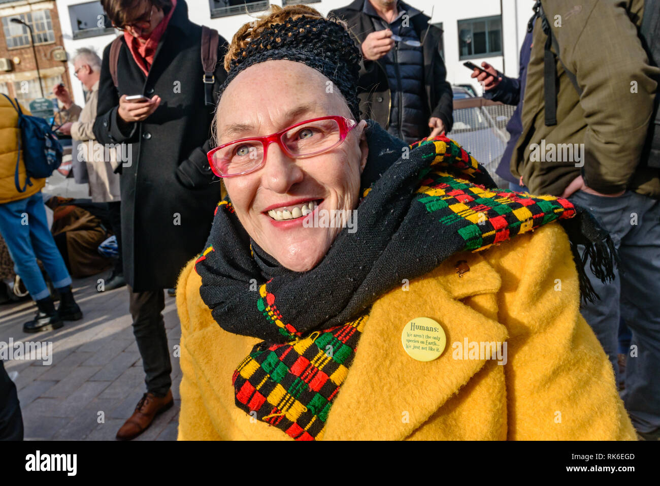 London, UK. 9th February 2019. A woman at the Extinction Rebellion street party wears a bade 'Humans: We aren't the only species on Earth... We just aci like it.'  XR is in open Rebellion against the UK Government for its criminal inaction in the face of impending climate and ecological collapse and held a street party blocking the A10 Kingsland High St in Dalston for two hours with speeches, music and spoken word performances, t-shirt printing, face painting and free food, with dancing to a samba band which led them for a brief march up the road before returning to continue the protest in Gil - Stock Image