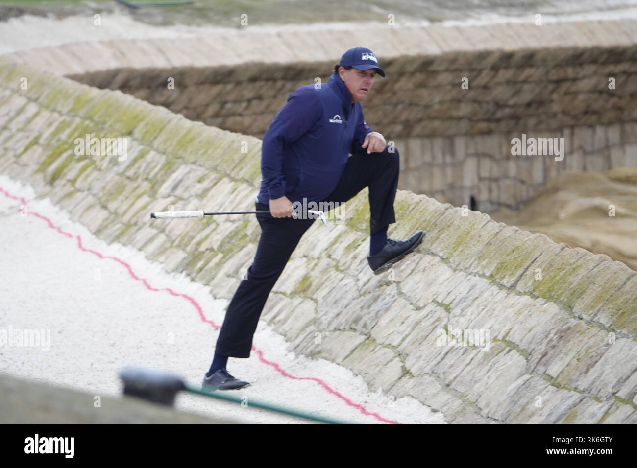 9th February, 2019  Pebble Beach Golf Links, CA, USA  Phil Mickleson strikes a pose on the sea wall defenses of the 18th as he trys to find playing partner Patrick Reed's errant ball during the third round at Pebble Beach Golf Course during the AT&T Pro-Am Credit: Motofoto/Alamy Live News - Stock Image