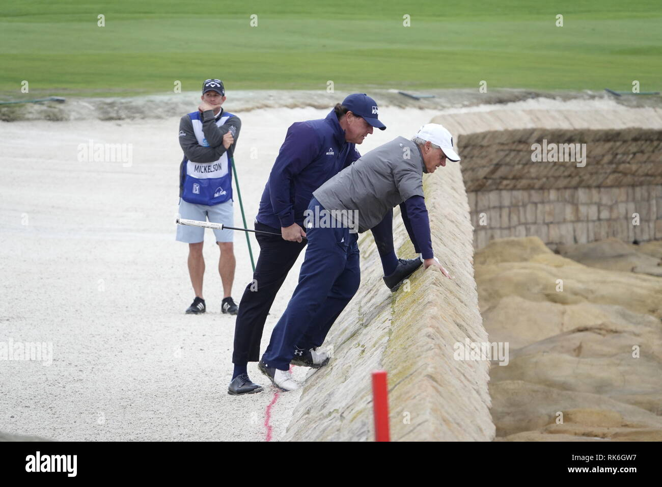 9th February, 2019  Pebble Beach Golf Links, CA, USA  Phil Mickleson and amateur partner Scott Ozanus strike a pose on the sea wall defenses of the 18th as he trys to find playing partner Patrick Reed's errant ball during the third round at Pebble Beach Golf Course during the AT&T Pro-Am Credit: Motofoto/Alamy Live News - Stock Image
