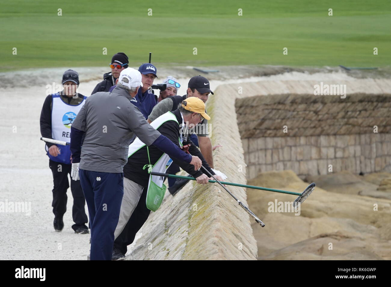 9th February, 2019  Pebble Beach Golf Links, CA, USA  Phil Mickleson and Patrick Reed and caddies search for Reeds  errant ball hit over the sea wall defenses of the 18th ball during the third round at Pebble Beach Golf Course during the AT&T Pro-Am Credit: Motofoto/Alamy Live News - Stock Image