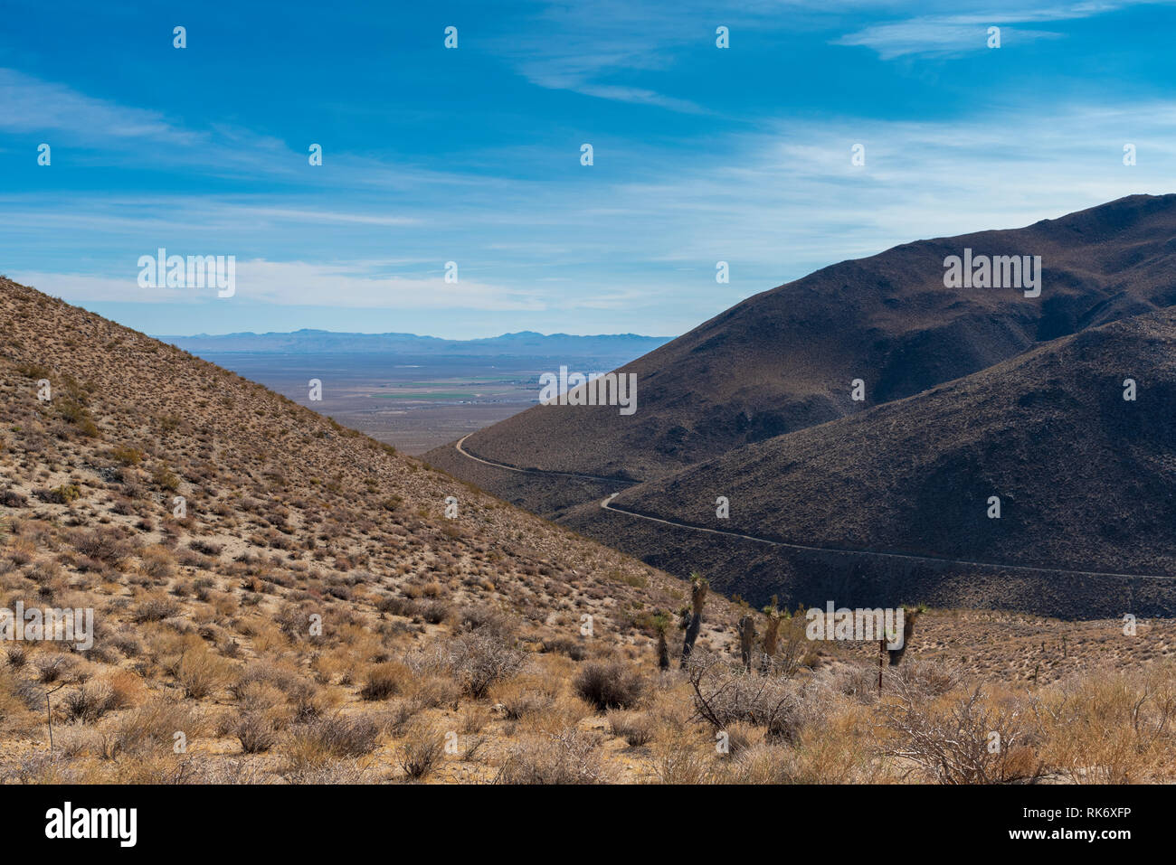 Looking down from mountain top at mountain, hills and valley below under bright blue sky with white clouds. Golden brown mountainside, desert brush. - Stock Image