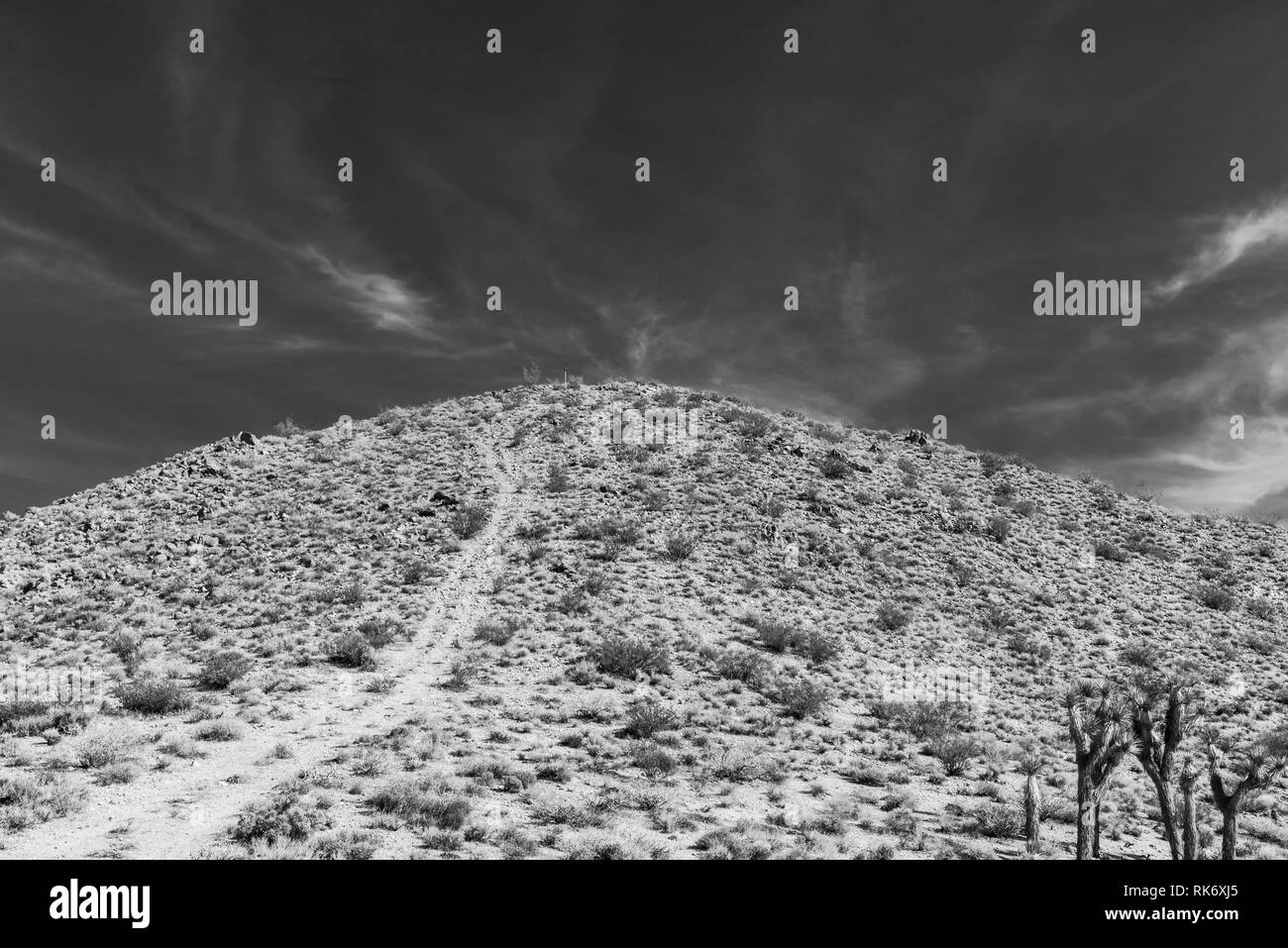 Dirt road leading up to top of desert mountainside under bright blue sky. Black and white. - Stock Image