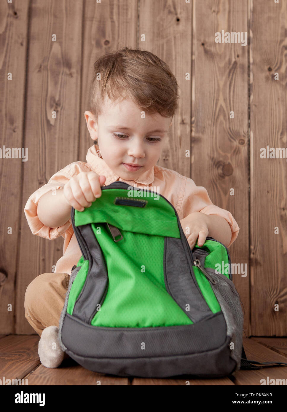 Little boy with large school bag on wooden background - Stock Image