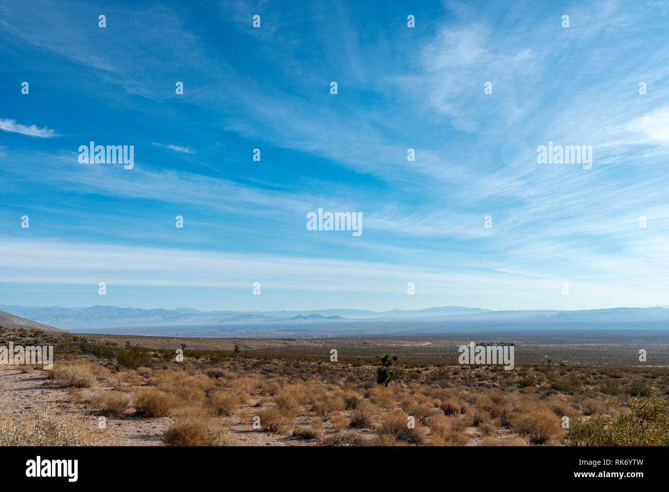 Looking down from top of desert valley with dead bushes and brush under blue sky with white clouds. Hazy mountains in the distance. - Stock Image