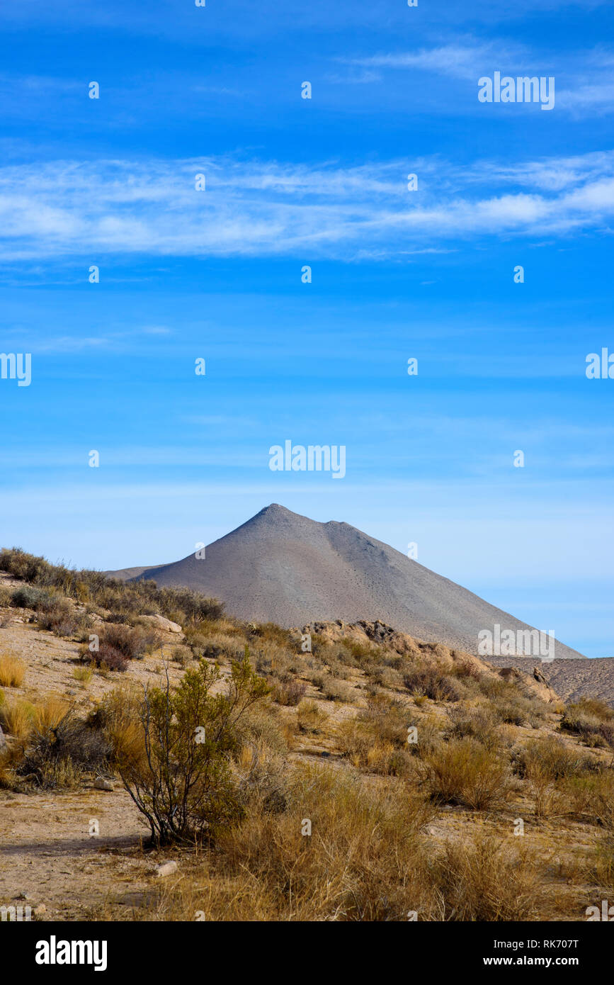 Desert brush on hillside with valley tall barren mountain beyond under bright blue sky with white clouds. - Stock Image