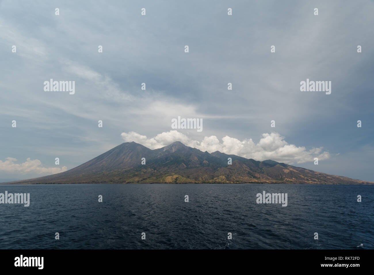 Ring of Fire island, Pulau Sangeang island  produces steam from its volcano - Stock Image