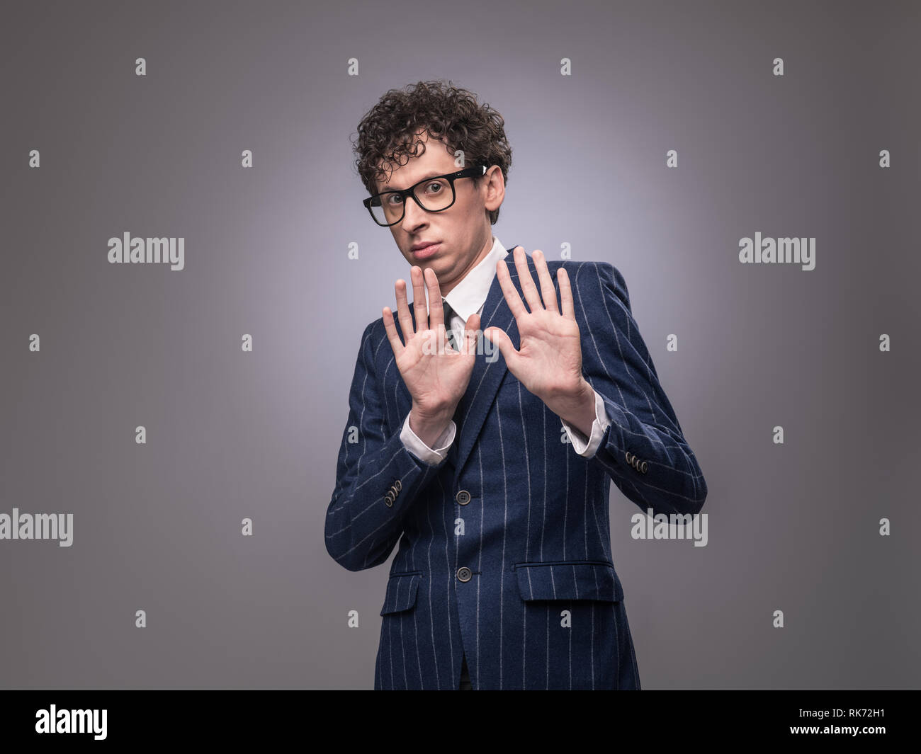 Shocked funny man in suit showing rejection sign and looking at camera. Uninterested businessman making stop gesture. Refusing concept - Stock Image