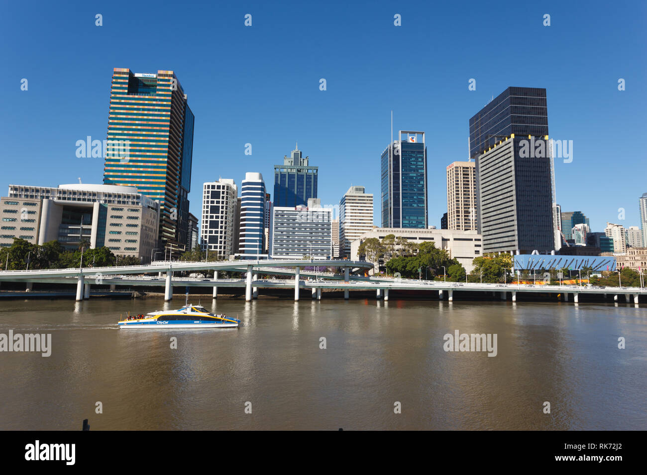 Ferry passes by city of Brisbane high rises and elevated roadway on a sunny day in Australia - Stock Image