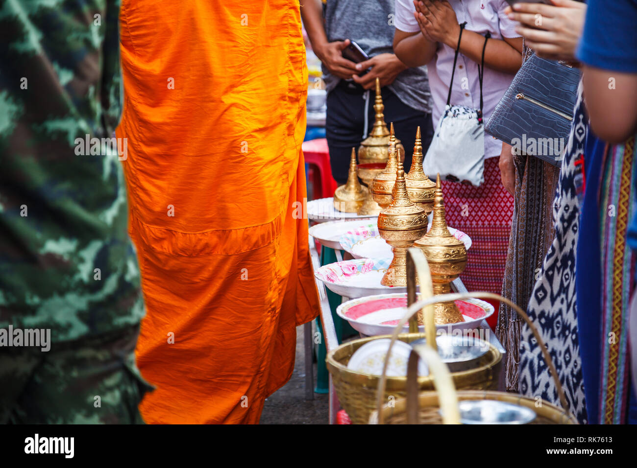 Laypeople make merits by giving food offerings to Buddhist monks going on daily alms round in morning at Mon Bridge, Sangkhlaburi, Kanchanaburi, Thail Stock Photo