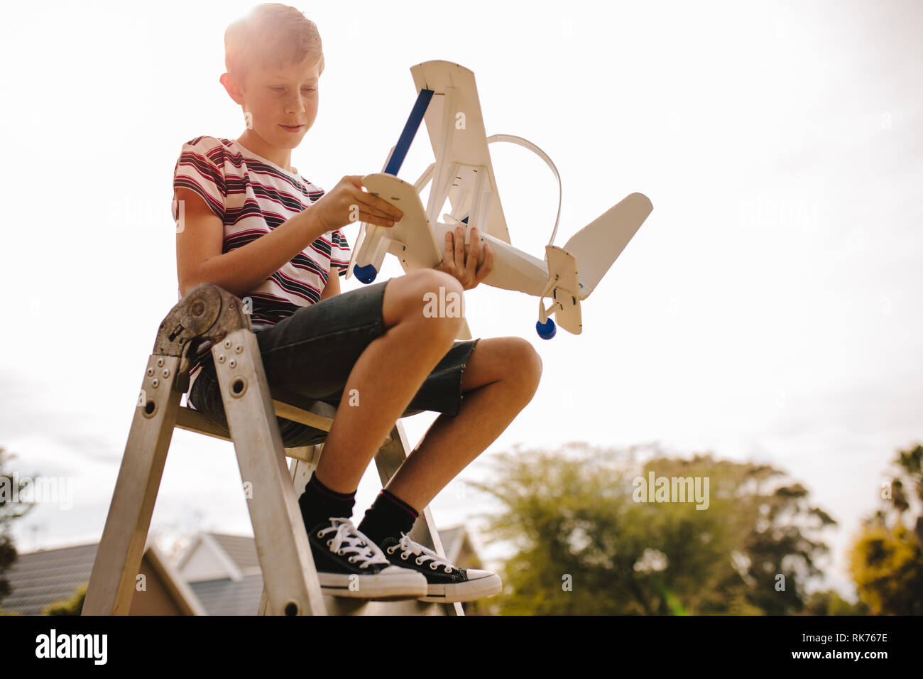 Boy sitting on top of a ladder and adjusting the toy airplane wing. Boy with toy aeroplane outdoors. - Stock Image