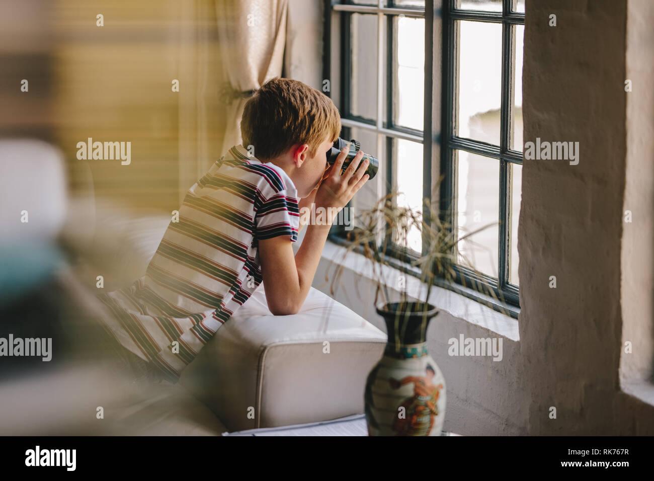 Boy on sofa looking outside window using binoculars. Curious boy looking out the window with binocular. - Stock Image