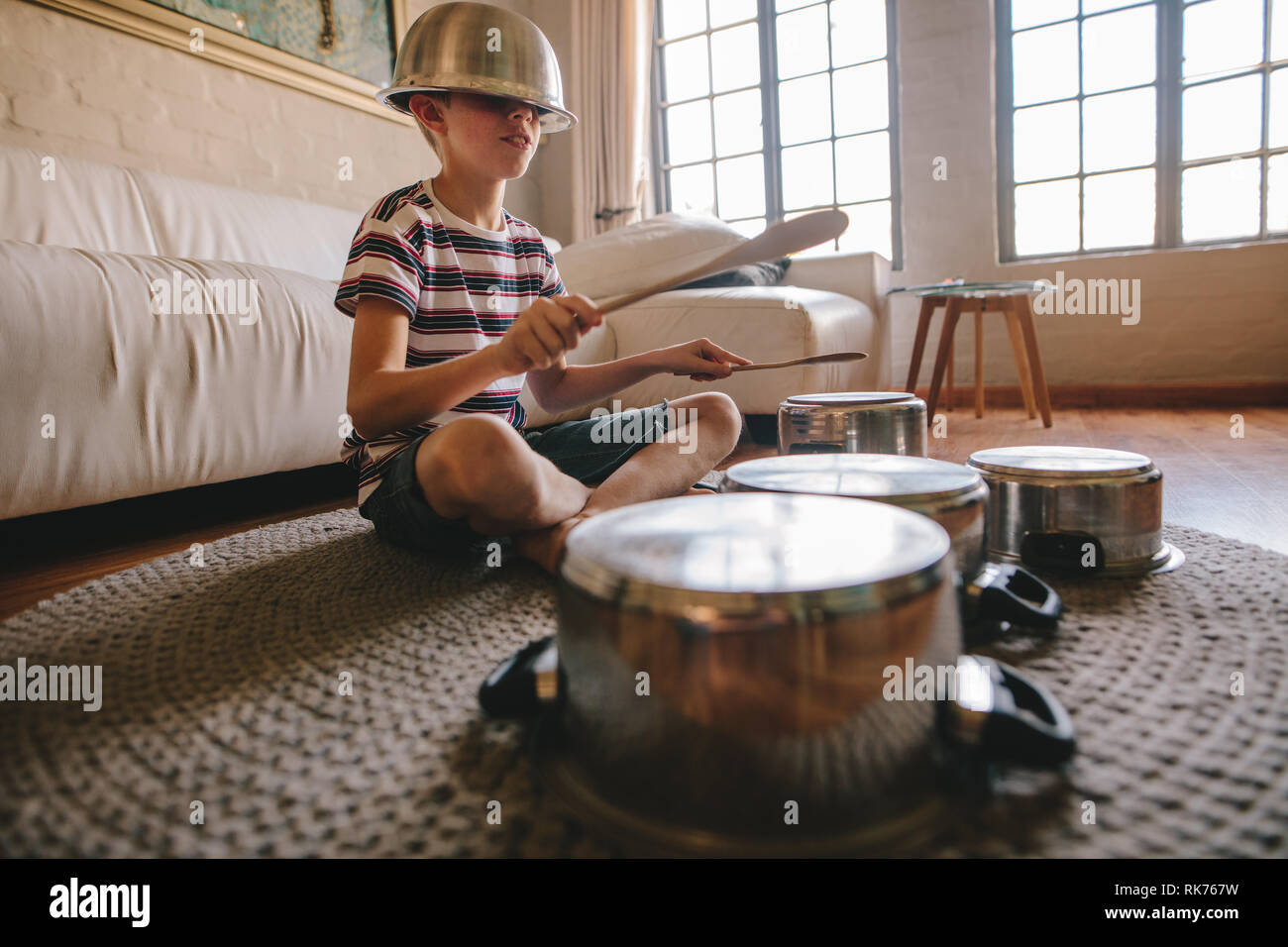 Boy playing drums on kitchenware at home. Boy pretending to be a drummer sitting on the living room floor and playing on utensils while wearing a bowl Stock Photo