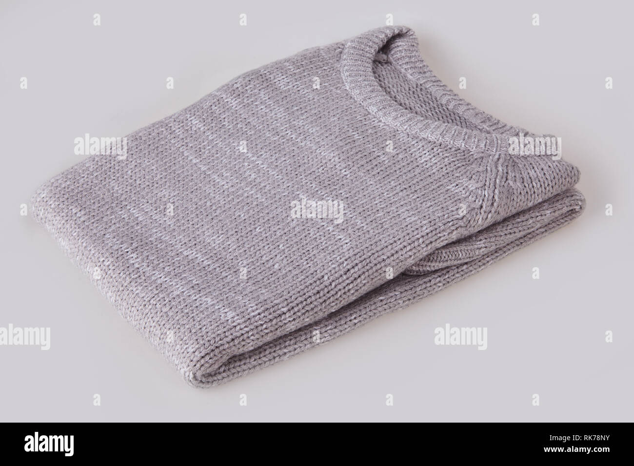 Gray folded knitted sweater with blank tag on white background. Clothes, fashion concept. Long sleeve tunic - Stock Image