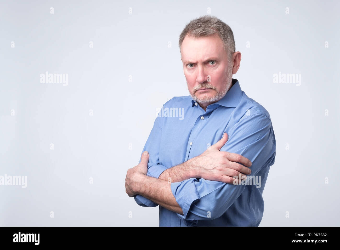 Serious senior man with folded arms and a deadpan expression posing on grey wall - Stock Image