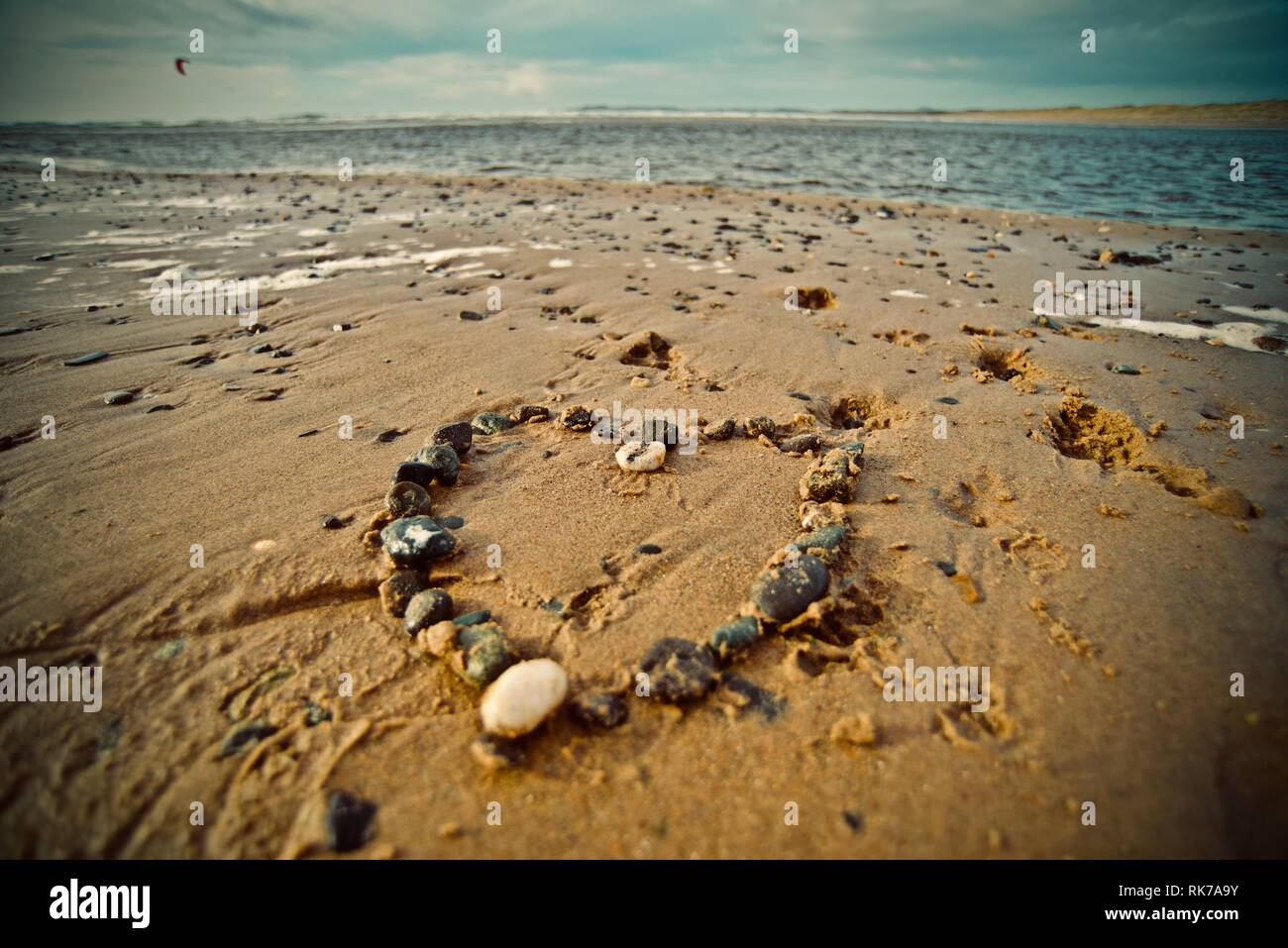 Love the beach, love the sea. A heart made of pebbles on the sand of a beach with the tide coming in, Rhosneigr, Anglesey, North Wales, UK Stock Photo