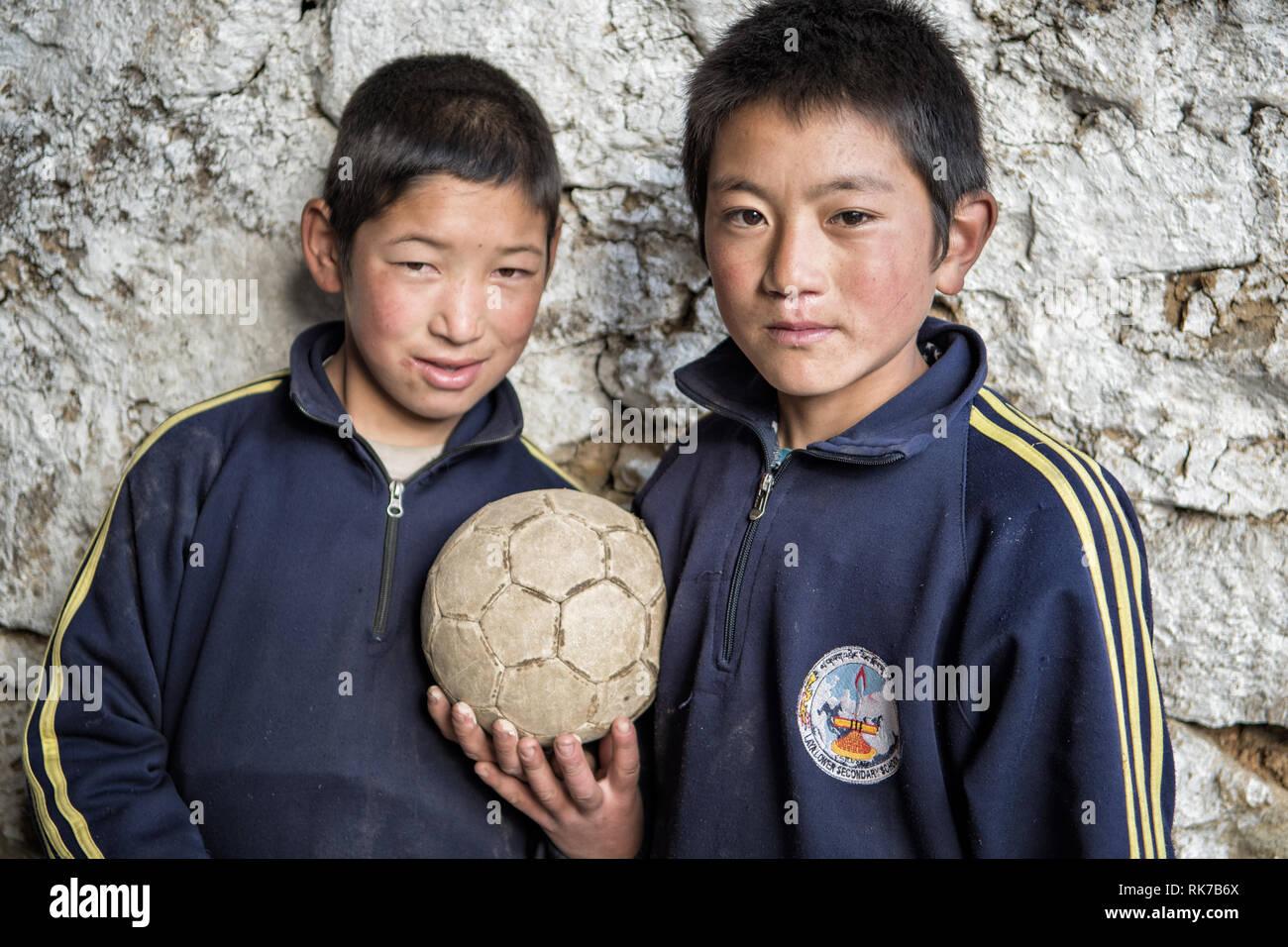 Two schoolchildren with a soccer ball in Laya, Gasa District, Snowman Trek, Bhutan - Stock Image