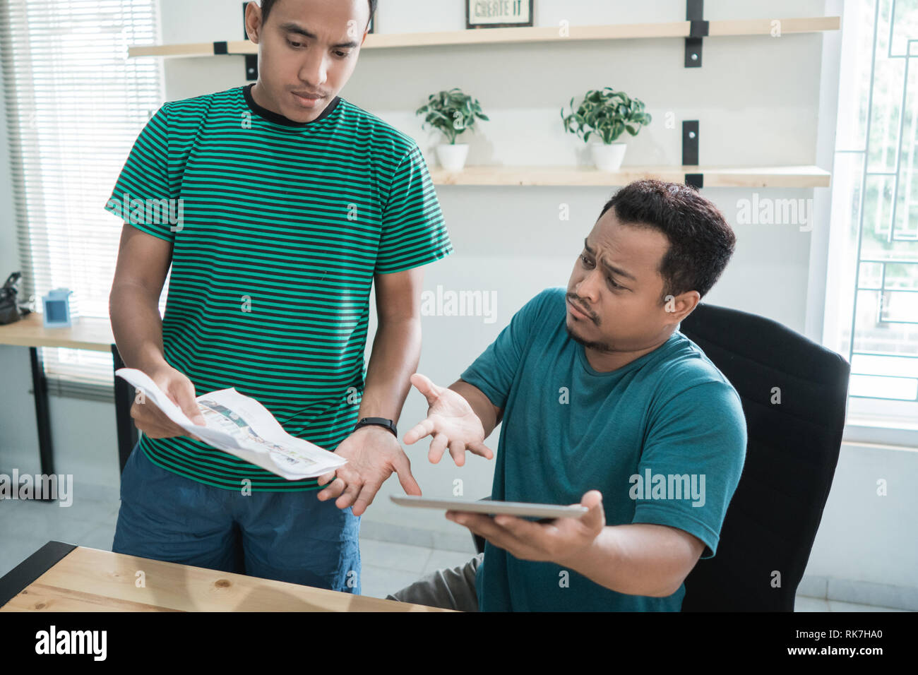 portrait of two young men dialogues and have  arguments about new project in the office room - Stock Image