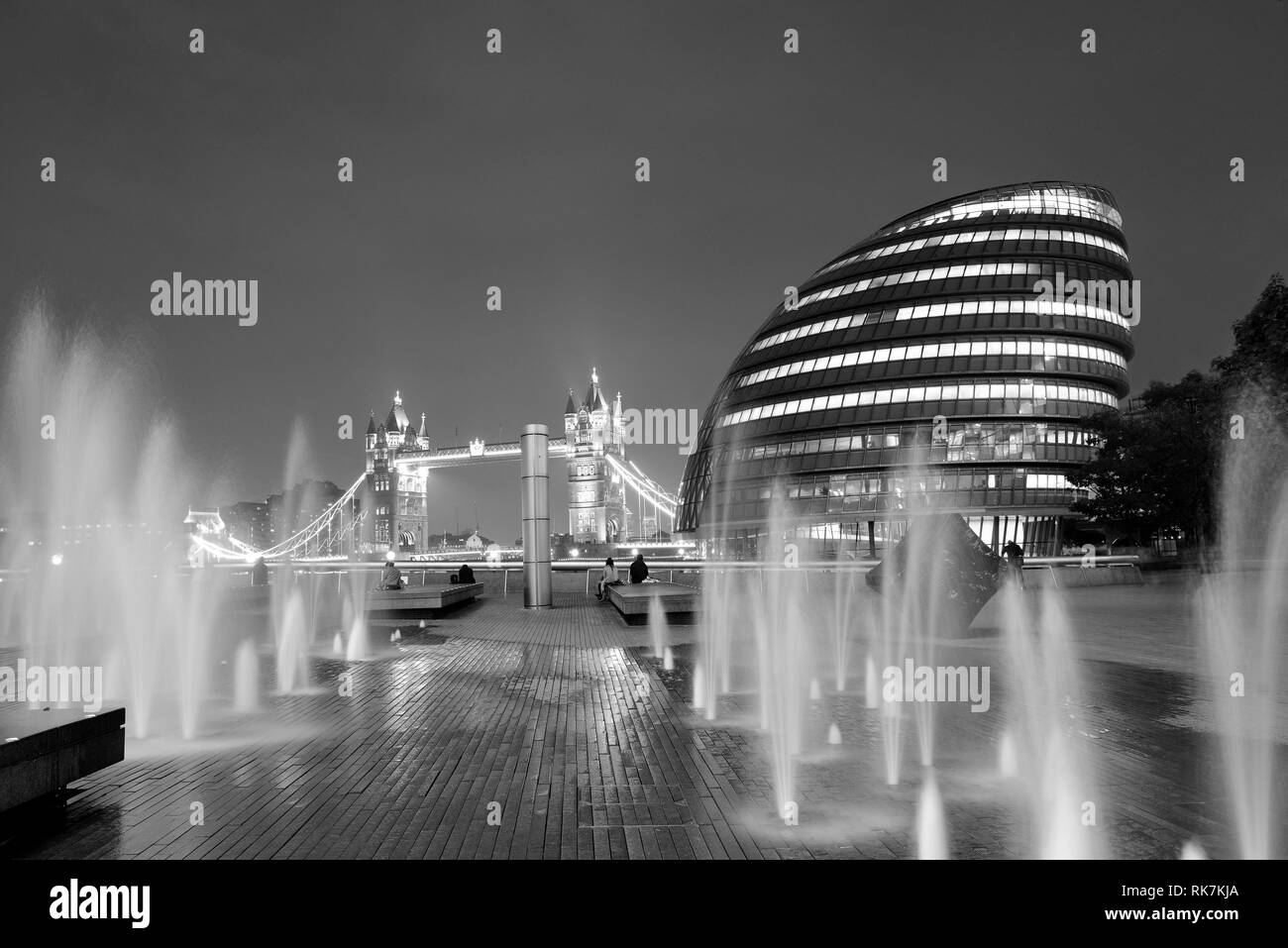 London Tower Bridge, City Hall and fountain at night in business district. - Stock Image