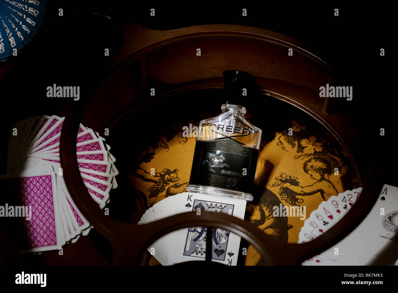 Close up look of Creed Aventus eau de parfum black, surrounded by paying cards in vintage cabinet. 05 December 2018, London. - Stock Image