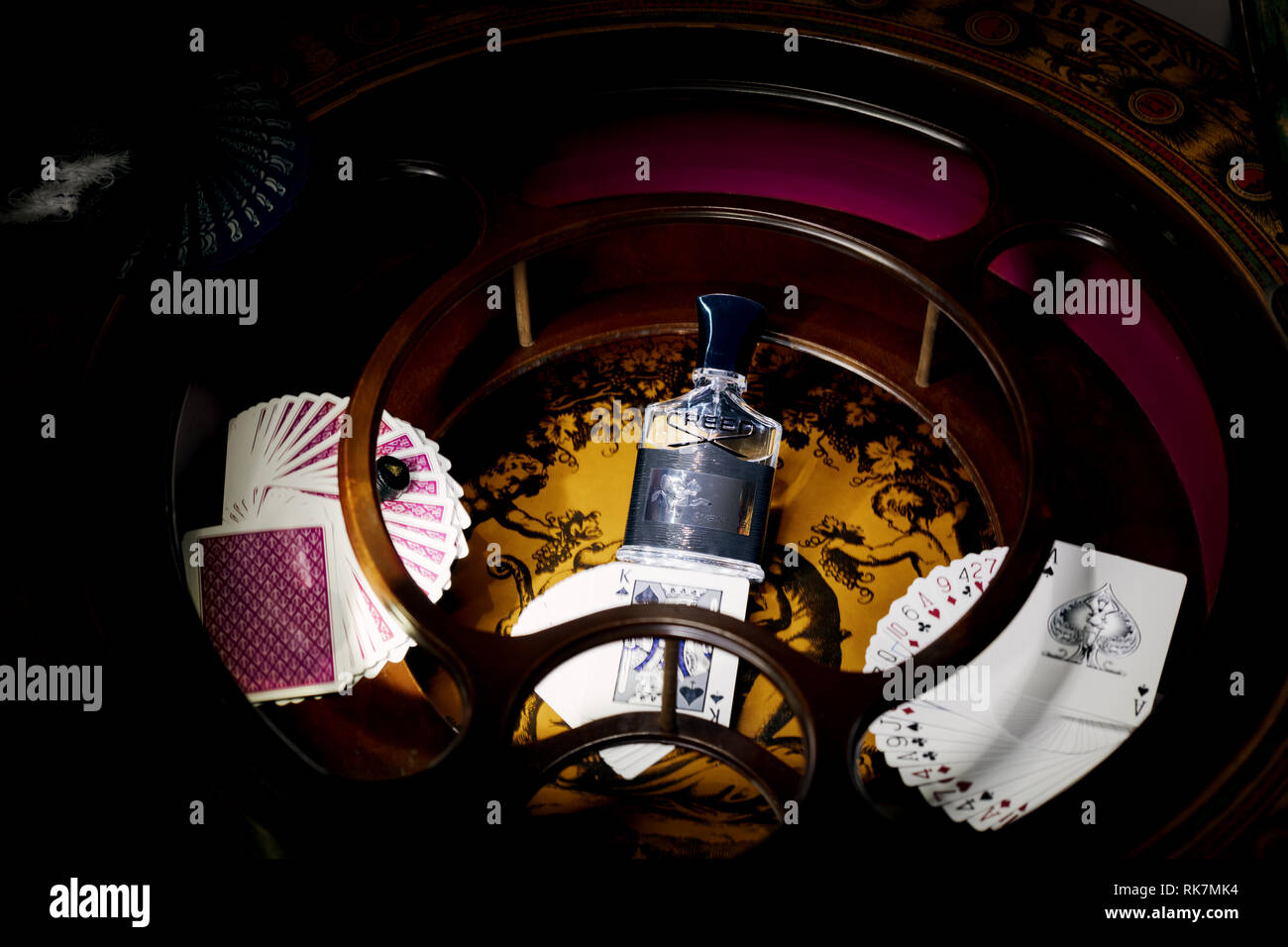 Creed Aventus eau de parfum black, surrounded by paying cards in vintage cabinet. 05 December 2018, London. - Stock Image