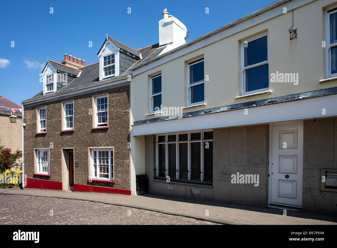 Well kept brightly painted houses at the bottom of Victoria Street on Alderney, Channel Islands. - Stock Image