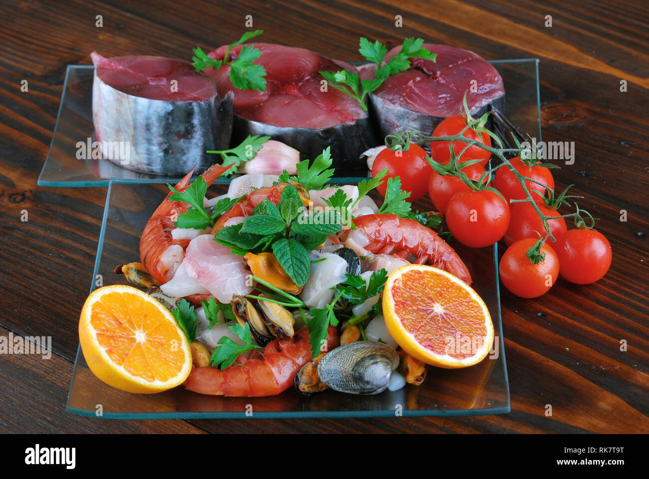 glass dishes with fish bonito mollusks and shellfish raw on the wooden board Stock Photo