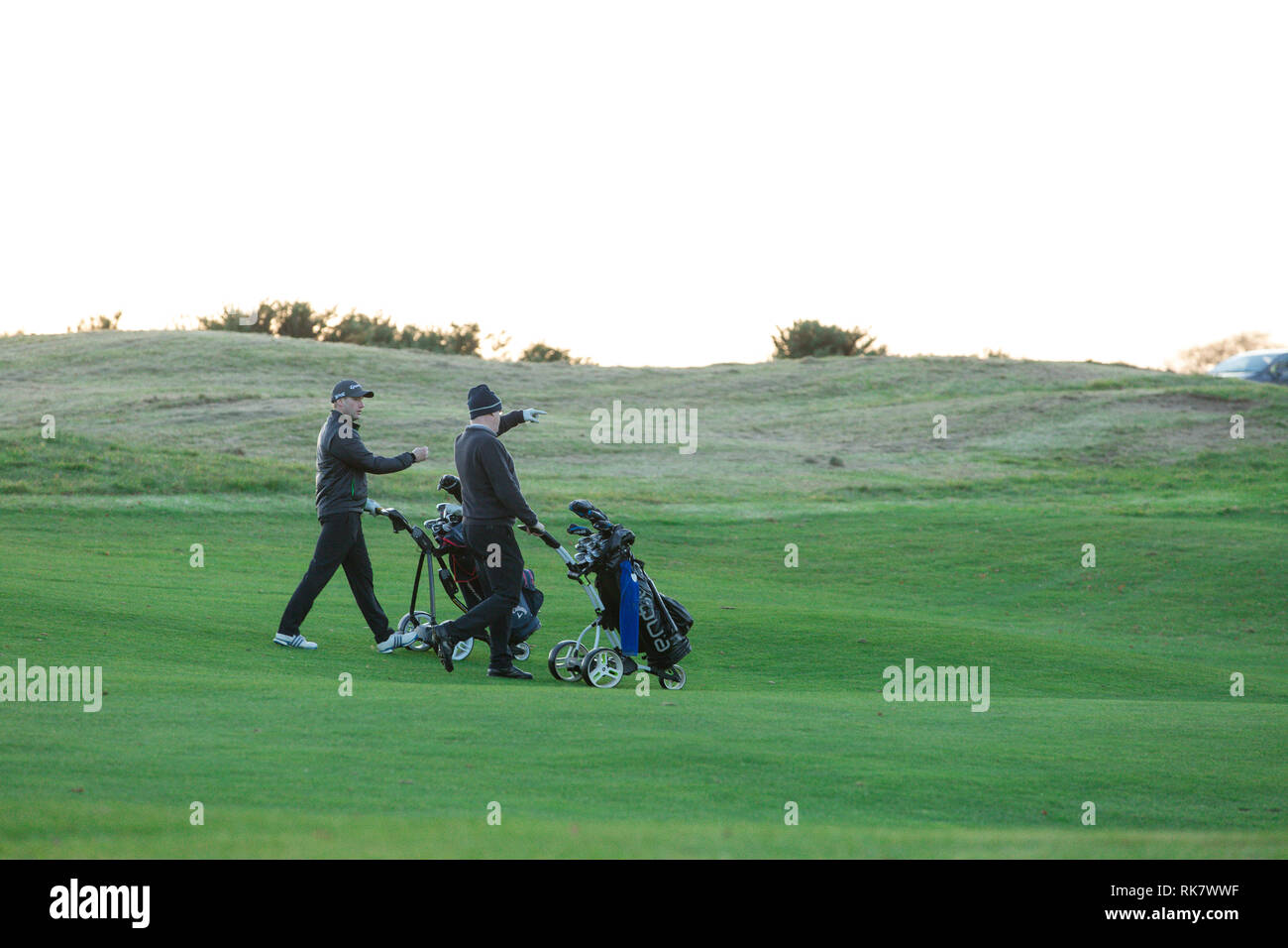 Two men wheeling trolleys with their golf bags through greens on the Carton House Golf Course in Maynooth, County Kildare, Ireland - Stock Image